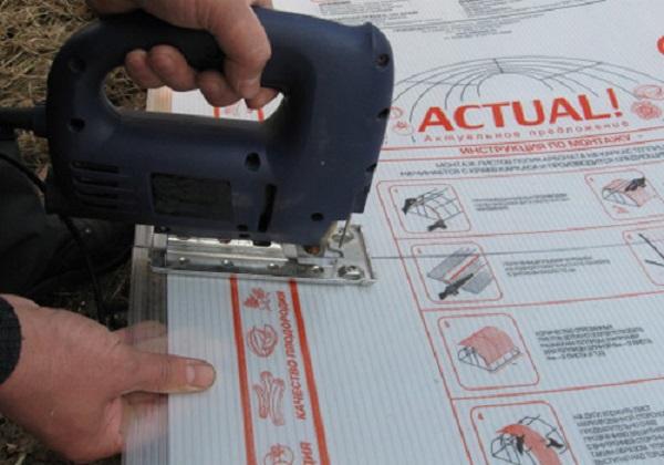 Завершение обрезки поликарбоната лобзиком. Если вы не желаете вставать на материал, даже при наличии доски-подмостки, то сначала выполните разрез с одной стороны, затем с противоположной