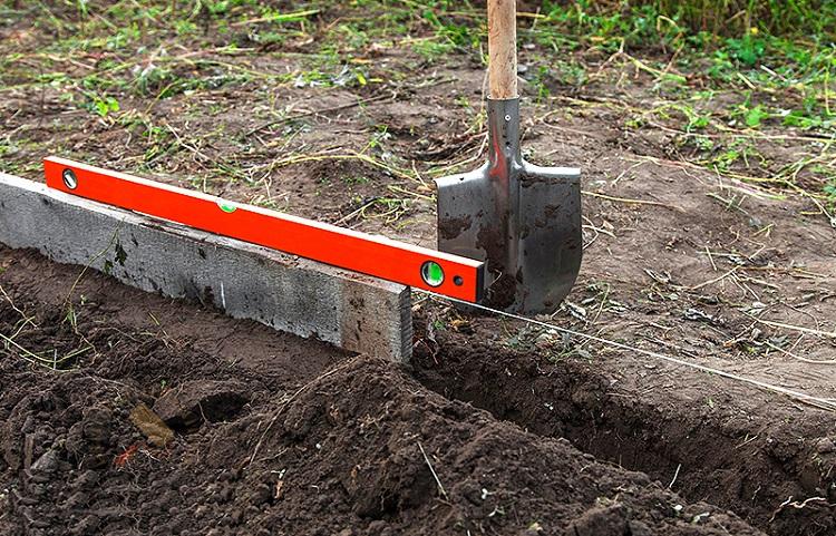 Прежде чем копать траншею, нужно отметить направление натянутым шнуром