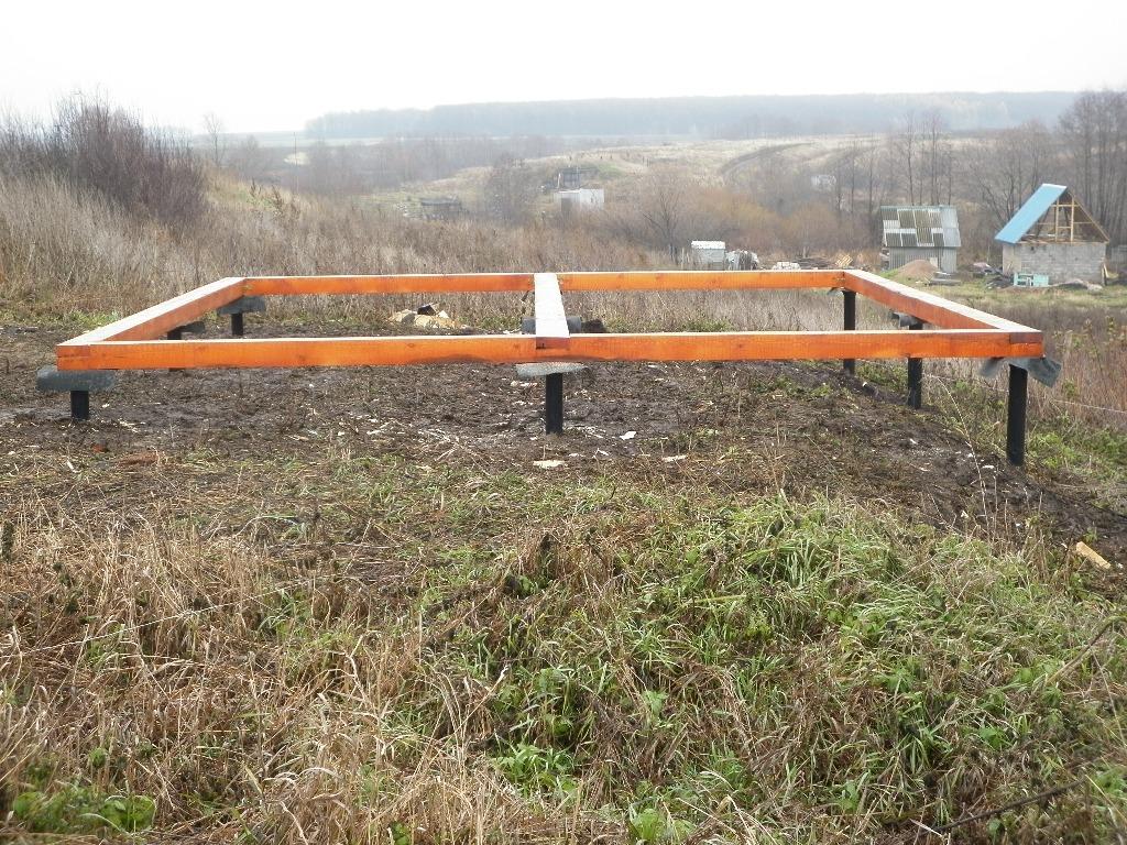 Пример свайного фундамента, обустроенного на участке с большим уклоном. Между ростверком и сваями можно увидеть слой гидроизоляции
