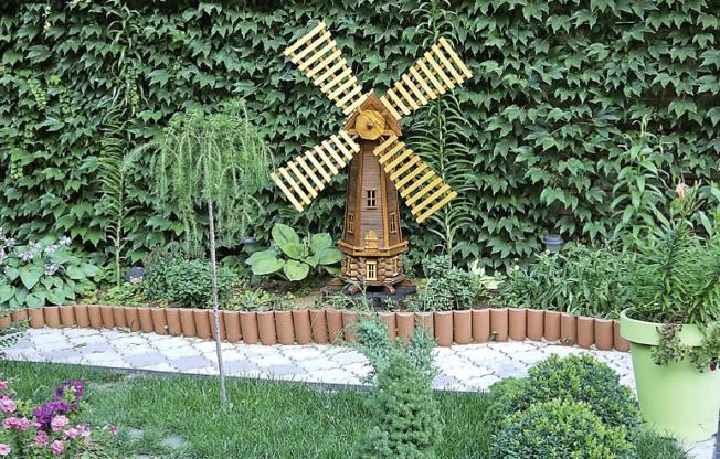 Готовая мельница-сруб, украшающая клумбу