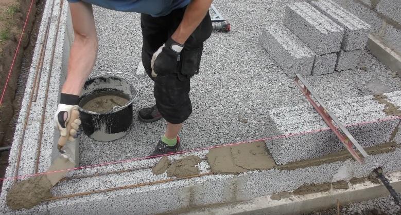 На фото видно пруты арматуры, уложенные между рядами блоков