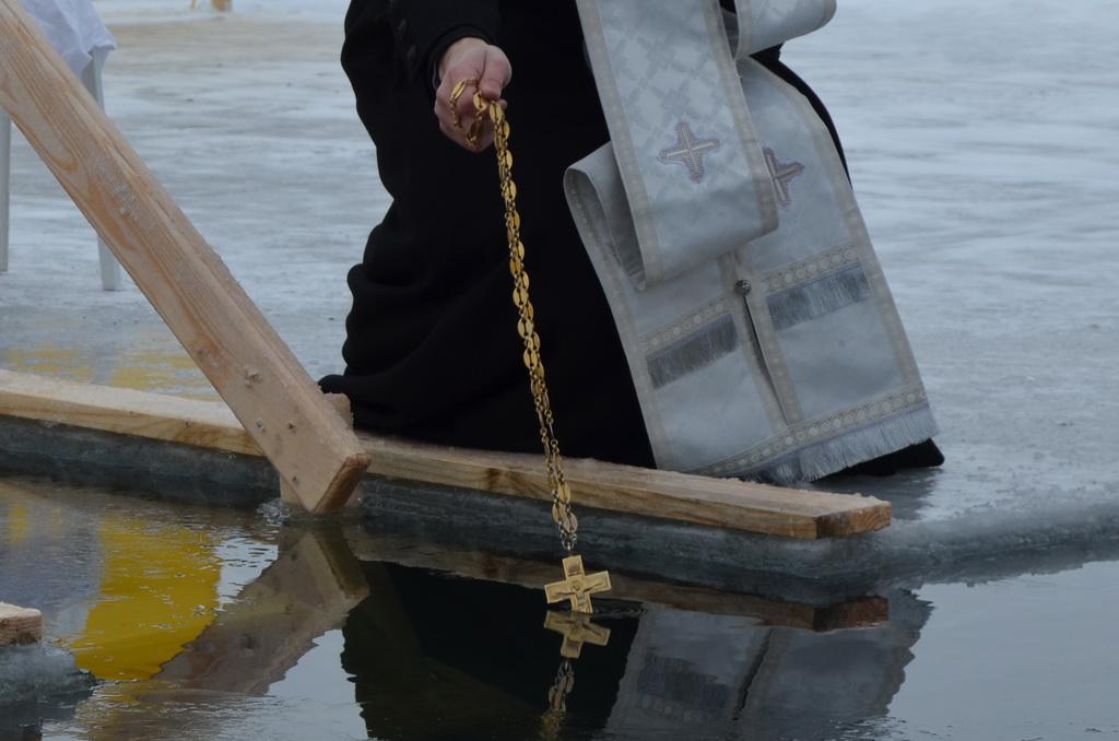 Священник опускает в воду крест во время обряда