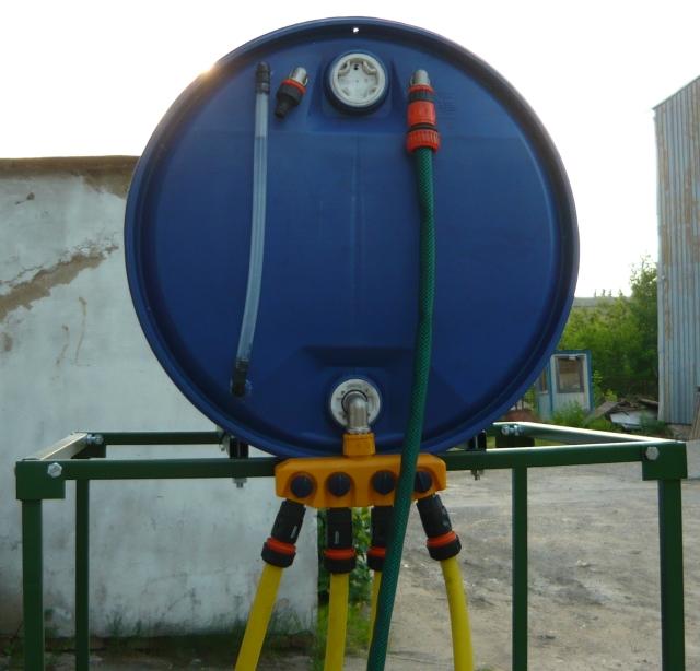 Небольшую емкость с водой имеет смысл установить на некотором возвышении – в трубе естественным путем создается давление, достаточное для работы капельного автоматического полива в одной из теплиц. Обратите также внимание на прозрачный шланг слева – он выступает в качестве своеобразного уровнемера, показывающего количество воды в емкости
