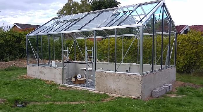 Практически завершенная теплица из стекла и алюминия. Остается только добавить двери и убрать строительный мусор