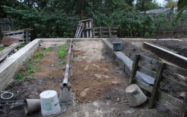 Заливка бетонной ленты для второй части экотеплицы с курятником и сараем. Столбы по центру создаются как опоры для перегородок, разделяющих помещения